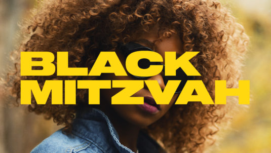 Black girl with great hair, sunglasses and Jen jacket with yellow title treatment over face
